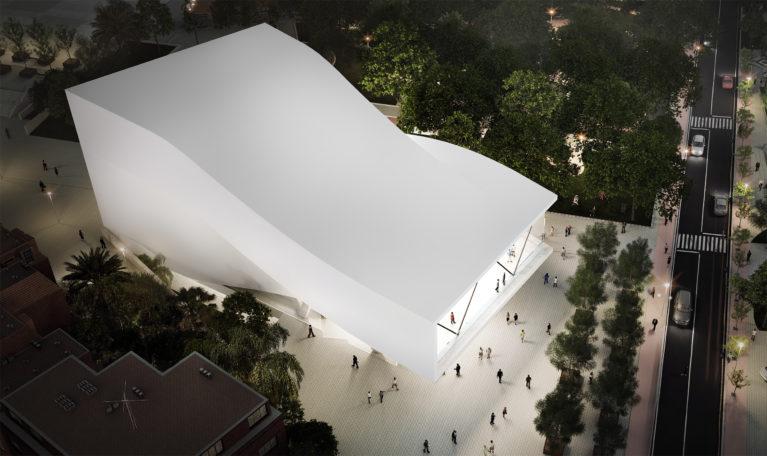 AQSO arquitectos office. Desde la vista de pájaro se aprecia la forma sinuosa de la cubierta del auditorio. Este edificio de hormigón blanco tiene unas forma plegada que se contrasta con la vegetación del parque urbano.