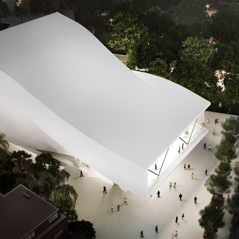 AQSO arquitectos office. A bird's eye view shows the sinuous shape of the auditorium roof. This white concrete building has a folded shape that contrasts with the vegetation of the urban park.