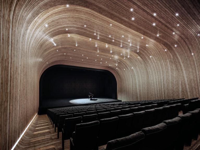 AQSO arquitectos office. Auditorio sin doblez, diseño interior, muros y techo acústico, piano en escenario, cascarón de madera, escalones iluminados, platea, salón de actos, diseño simple, impresionante auditorio