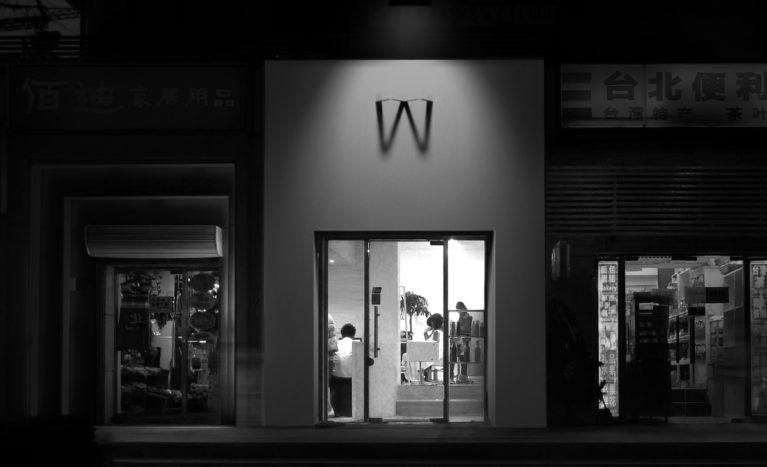AQSO arquitectos office. La fachada exterior del salón de peluquería tiene un cartel luminoso que proyecta la sombra de la letra W sobre una pared blanca. Es un cartel y un logo original.