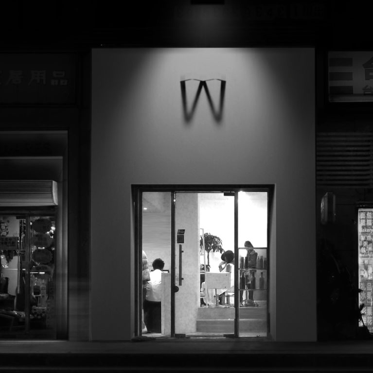 AQSO arquitectos office. The exterior façade of the hairdressing salon has an illuminated sign that casts the shadow of the letter W on a white wall. It is an original sign and logo.