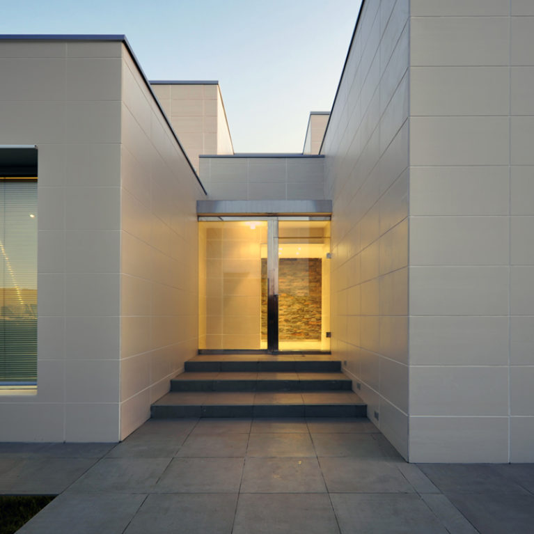 AQSO arquitectos office. Contemporary single-family house with flat roof. The building is made up of different volumes and the façade is covered with ceramic tiles.