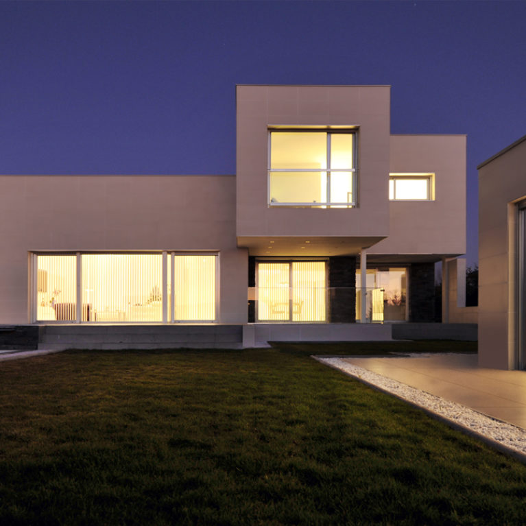 AQSO arquitectos office. The main façade of the house has large windows and a cantilevered section overlooking the garden where there is a swimming pool and a gazebo.