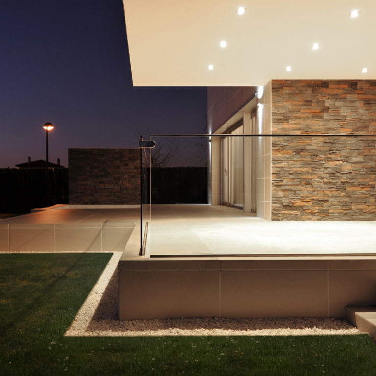 AQSO arquitectos office. The front porch of this contemporary home has a glass balustrade and is covered by an cantilever.