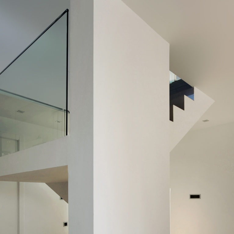 AQSO arquitectos office. The stairs are a central feature in the entrance hall, a sculptural and minimalist element with a glass balustrade.