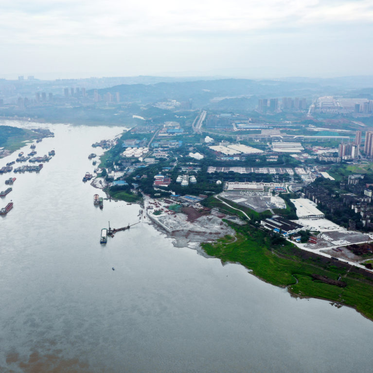 AQSO arquitectos office. Aerial view of the Tangiatuo district in Chongqing city. The new urban design integrates the industrial character of the riverside with a new sustainable approach.