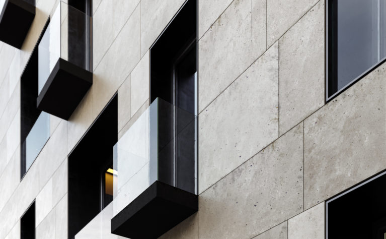 AQSO arquitectos office. Detail of one of the balconies. A simple slab cladded with dark metal protrudes from the facade plane with a frameless glass balustrade, contrasting with the limestone cladding.