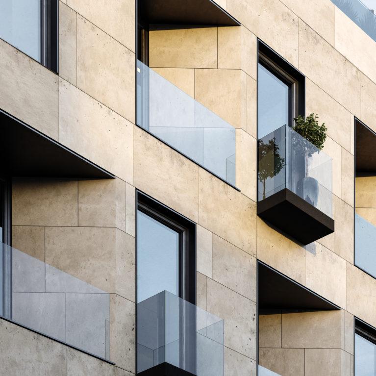 AQSO arquitectos office. La impresionante fachada del edificio Lofts Maragatos está compuesta de balcones y miradores, combinando piedra caliza, cercos de metal y compuestos de aluminio.