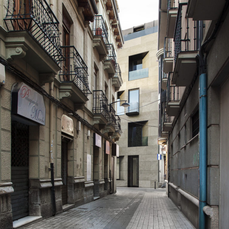 AQSO arquitectos office. The building, seen from the narrow adjacent street, shows the balconies and windows capturing the views of the urban setting.