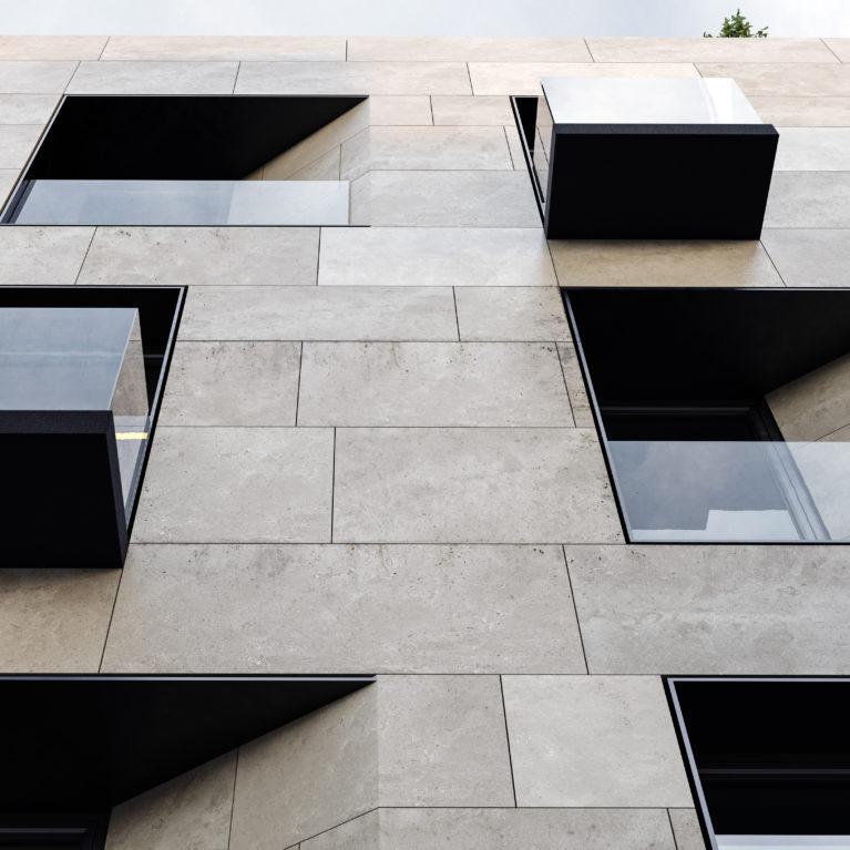 AQSO arquitectos office. La sobria fachada combina tres materiales: piedra arenisca, metal oscuro y vidrio. La disposición de los huecos ofrece un aspecto dinámico basado en simples desplazamientos, esquinas achaflanadas y alineación de huecos.