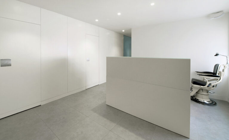 AQSO arquitectos office. The Zurbarán clinic has a white lacquered wooden counter in the dentist's consulting room. It is a simple and minimalist interior design in white.