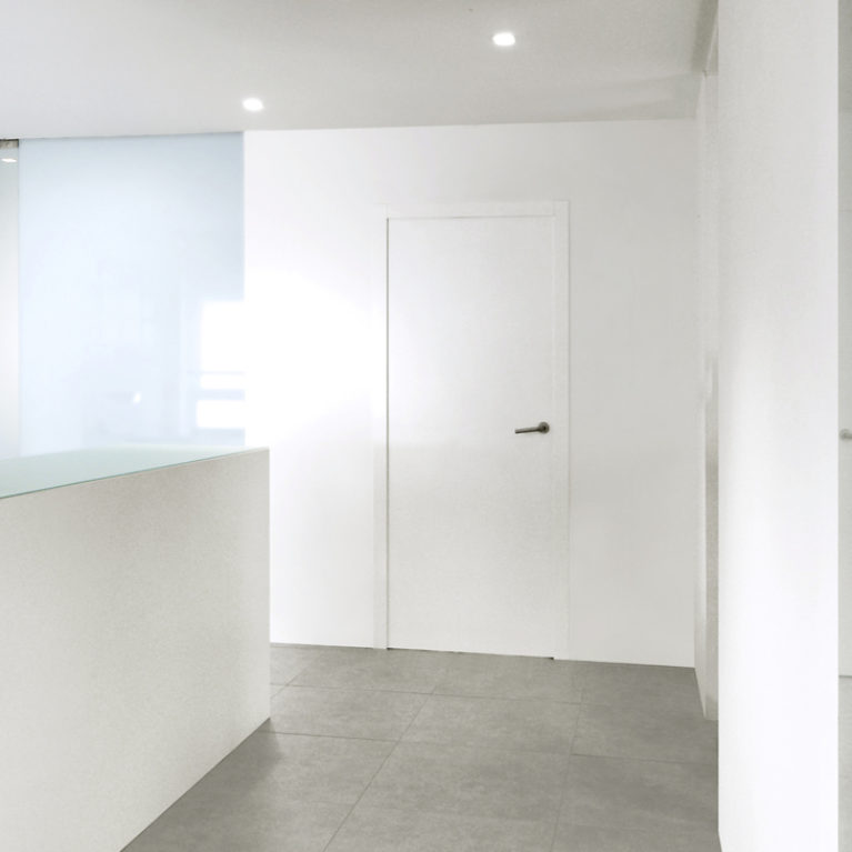 AQSO arquitectos office. The entrance of this mimimalist clinic has simple white walls panelled with lacquered wooden boards on which the reception desk is integrated.