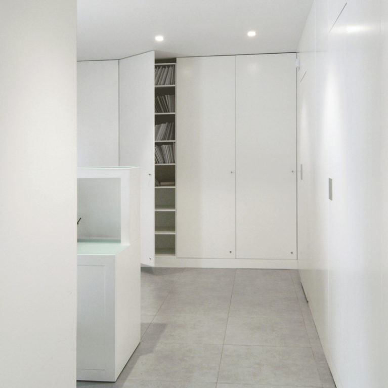 AQSO arquitectos office. The corridors of this clinic are lined with floor-to-ceiling cabinets with minimalist white lacquered MDF doors.