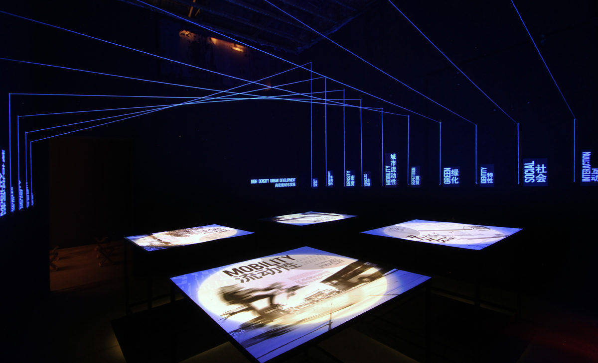 AQSO arquitectos office. La sala de exposiciones cuenta con cuatro mesas iluminadas con infografías e ilustraciones que explican los cuatro fundamentos del urbanismo.