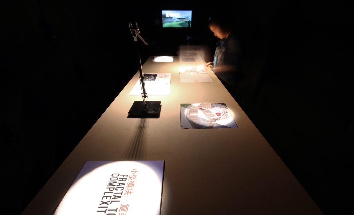 AQSO arquitectos office. El espacio expositivo es una sala oscura en la que destacan las mesas alargadas con paneles giratorios interactivos, libros y pantallas con vídeos.