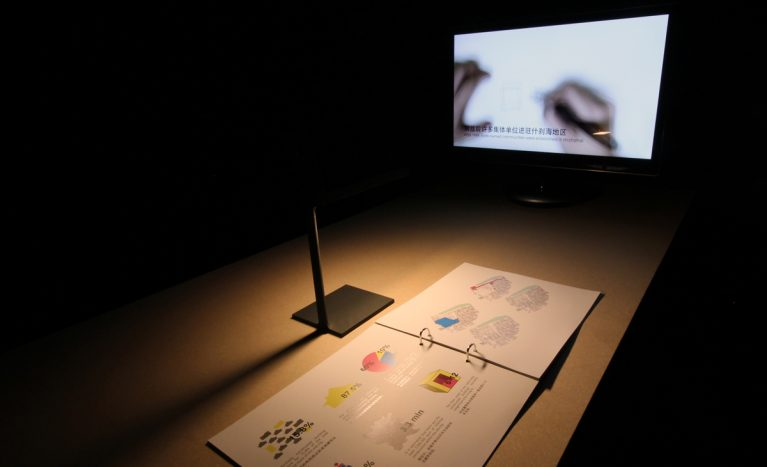 AQSO arquitectos office. Each project in the exhibition is displayed on a table with a book containing graphic content and a screen with a documentary video.
