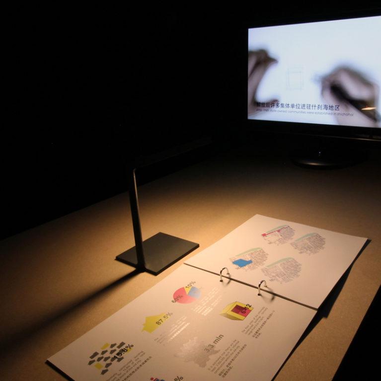 AQSO arquitectos office. Cada proyecto de la exposición se muestra en una mesa que tiene un libro con contenido gráfico y una pantalla con un vídeo documental.