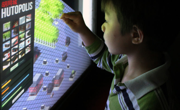 AQSO arquitectos office. A child interacts with the touch screen of the exhibition which, like an urban game, allows you to drag and drop elements in the urban space to create your own hutong.