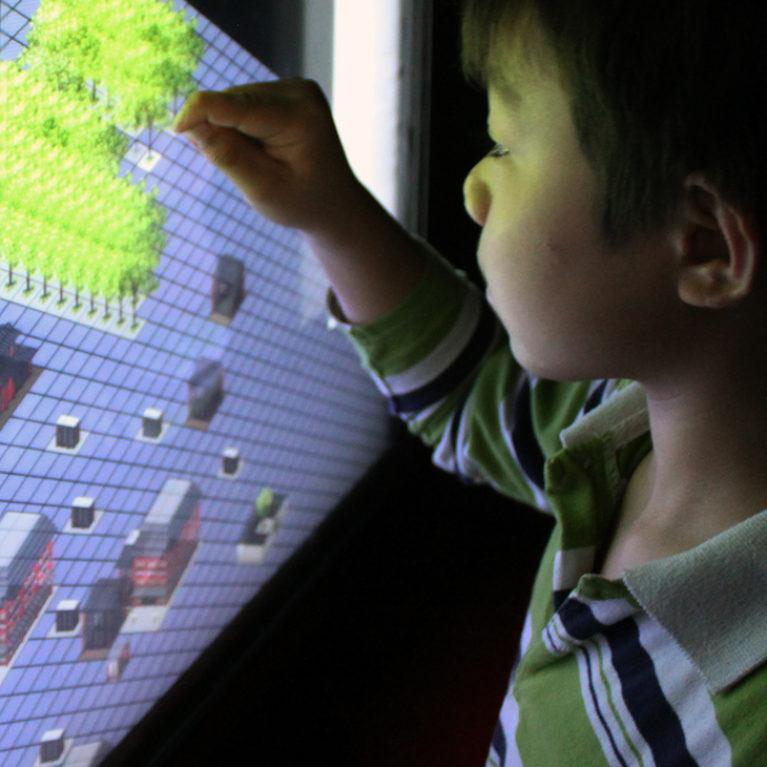 AQSO arquitectos office. Un niño interactúa con la pantalla táctiil de la exposición que, como un juego urbano, permite arrastrar y soltar elementos en el espacio urbano para crear tu propio hutong.