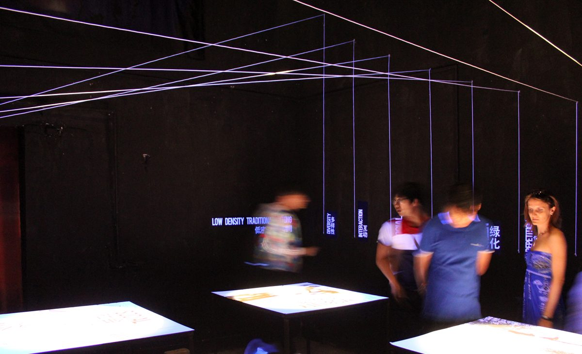 AQSO arquitectos office. The main exhibition hall is a dark space with four illuminated tables corresponding to the principles of urban research.