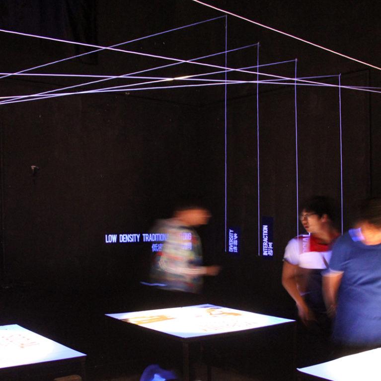 AQSO arquitectos office. La sala de exposiciones princial es un espacio oscuro con cuatro mesas iluminadas que corresponden a los principios de la investigación urbana.