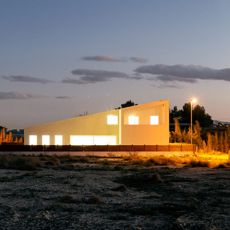 AQSO arquitectos office. The exterior view of the house, with the sloping roof, the white walls and the simple, modern silhouette that stands out against the landscape.