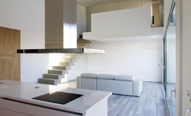 AQSO aquitectos office. The kitchen, living room and dining room are located on the ground floor, from where a concrete staircase leads up to the bedrooms.