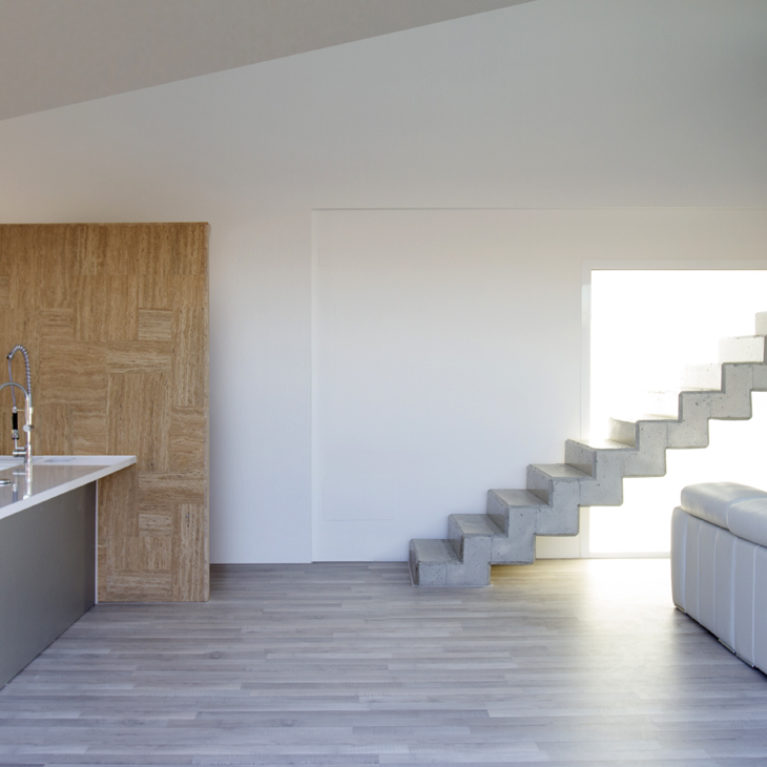 AQSO arquitectos office. The interior of the house combines grey wooden floors with travertine stone and the exposed concrete of the stairs.