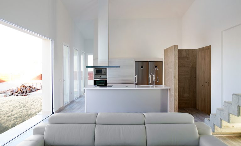 AQSO arquitectos office. From the open-plan living area you can see the kitchen with a central island, a double fridge and an extractor fan hanging from the ceiling.