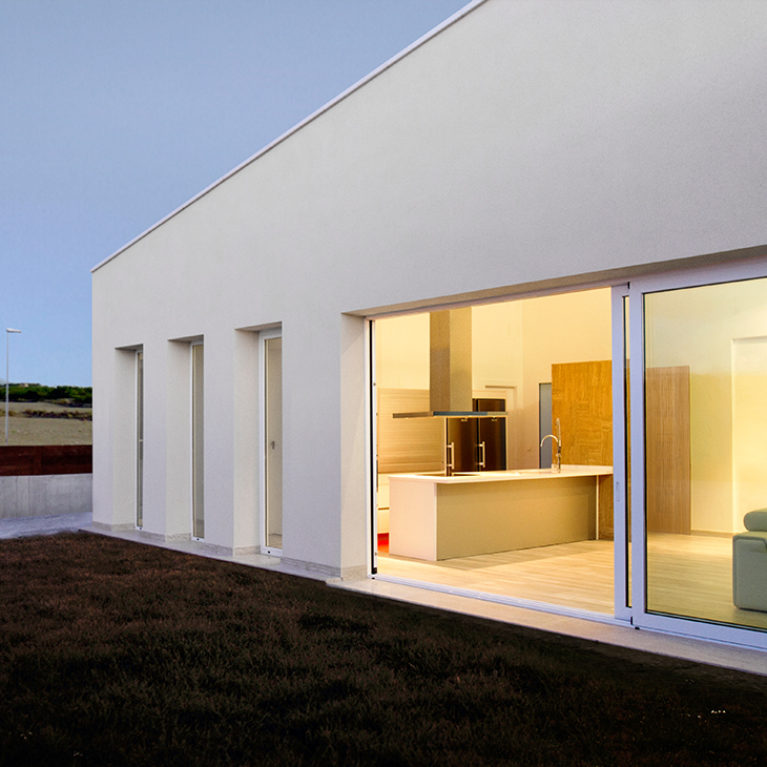 AQSO arquitectos office. In the evening, the large living room window illuminates the front garden, from which you can see the white mountains surrounding the house.