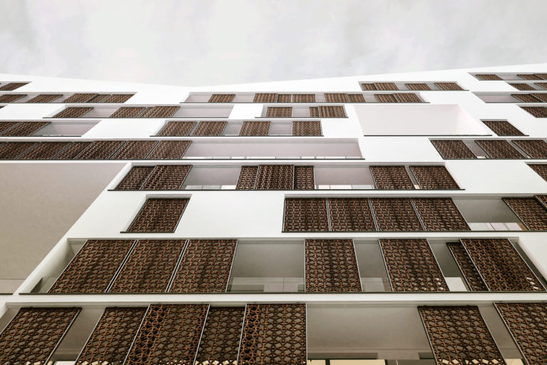 aqso arquitectos office, detail of the external building facade, where the Moroccan-inspired lattice of the sliding panels screens on metal rails protects from the sun the generous balconies facing the boulevard.