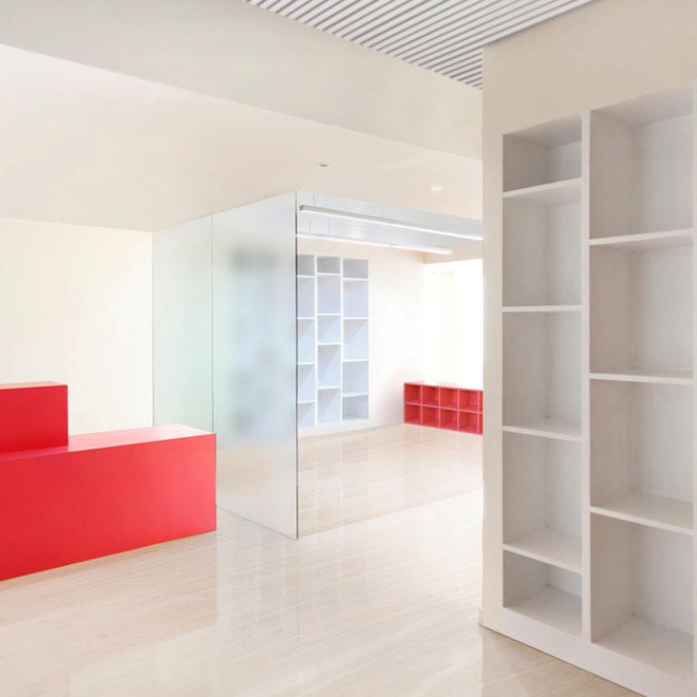 AQSO arquitectos office. La entrada tiene una sala de espera que conecta con la zona de talleres. El diseño interior es luminoso y combina particiones de vidrio translúcido con muebles sencillos de colores.
