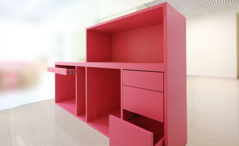 AQSO arquitectos office. The reception desk is a two-height piece of furniture with a PC keyboard tray and several drawers made of pink lacquered MDF.