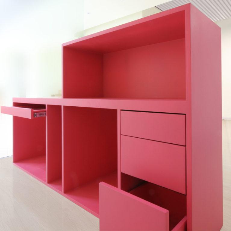 AQSO arquitectos office. El mostrador de recepción es un mueble a dos alturas que cuenta con una bandeja para el teclado del PC y varios cajones hechos de MDF lacado en rosa.