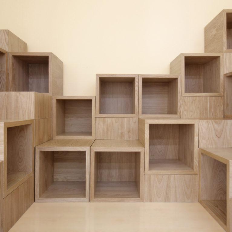 AQSO arquitectos office. La biblioteca infantil está formada por una composición de cubos de madera que pueden agruparse para formar un mueble escalable donde guardar libros y sentarse a leer.