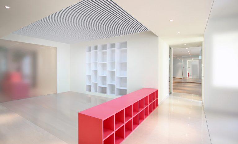 AQSO arquitectos office. En en la parte central del local se sitúa la zona de talleres, que cuenta con un mueble bajo de madera lacada de color rosa y una estantería integrada en la pared.