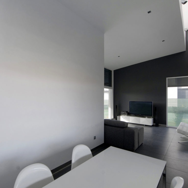 AQSO arquitectos office. The dining room is a transition space to the living room in this open-plan flat. The space is illuminated by the skylight in the ceiling and the large windows facing the garden.