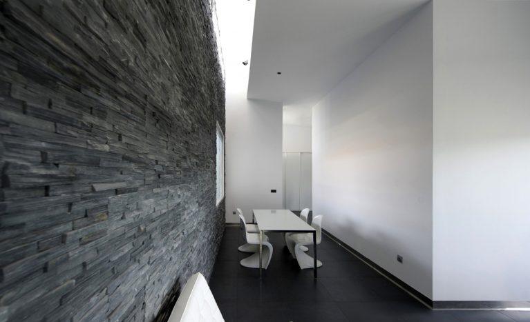 AQSO arquitectos office. El interior de la sala de estar tiene un muro de piedra natural de color negro iluminado por un lucernario. La mesa de comedor está rodeada de las sillas apilables diseñadas por Vener Panton.