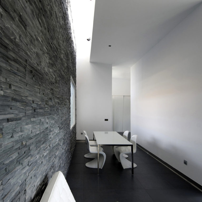 AQSO arquitectos office. The interior of the living room has a black natural stone wall illuminated by a skylight. The dining table is surrounded by stackable chairs designed by Vener Panton.