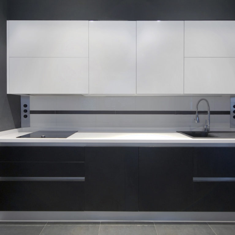 AQSO arquitectos office. The kitchen is separate from the living room and is open to the garden. The modular furniture is minimalist and made of dark natural wood and white lacquered doors.