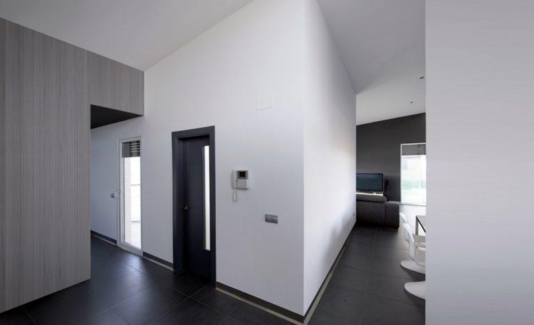AQSO arquitectos office. La vivienda se distribuye en torno a la cocina y el jardín. El tejado inclinado proporciona mayor altura al techo del salón y desciende hacia los dormitorios.