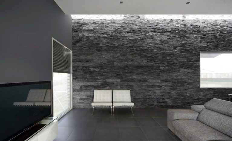 AQSO arquitectos officce. El corazón de la vivienda es el salón, iluminado por grandes ventanas y un lucernario. Las paredes oscuras contrastan con el techo y los sillones Barcelona de cuero blanco diseñados por Mies van Der Rohe.