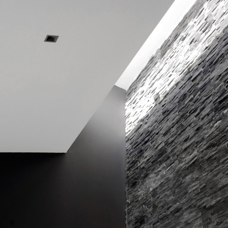 AQSO arquitectos office. The elongated skylight that opens up the roof along the stone wall emphasises the texture of the slate masonry and contrasts with the black painted wall.