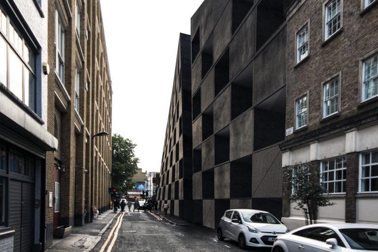 AQSO arquitectos office. El alzado lateral del hotel extiende el patrón de ajedrez de la fachada de hormigón negro.