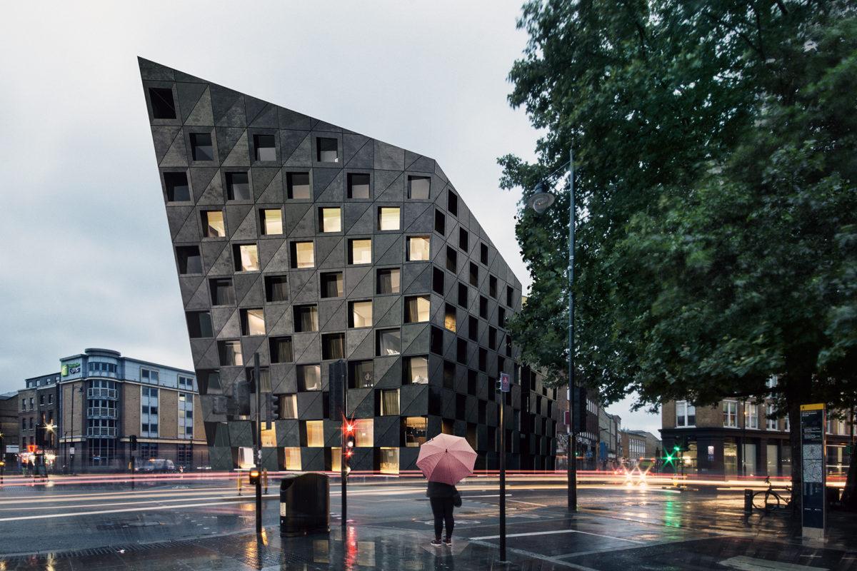 AQSO arquitectos office. Vista nocturna del hotel, donde la luz de las ventanas subraya el patrón ajedrezado de la fachada de hormigón negro, creando un icono urbano fácilmente reconocible.