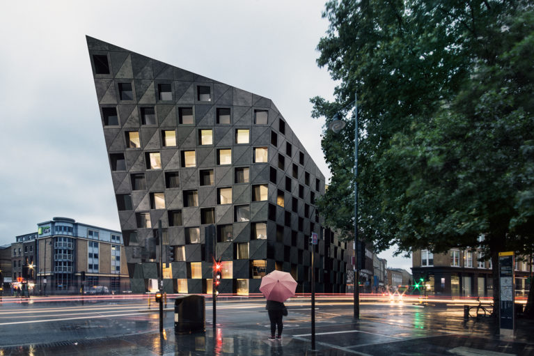 AQSO arquitectos office. Night view of the hotel, where the light from the windows underlines the chequered pattern of the black concrete façade, creating an easily recognisable urban icon.