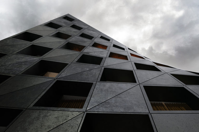 AQSO arquitectos office. Prefabricated facade made of lightweight concrete forming an ruled surface. Each of the windows corresponds to a hotel room.