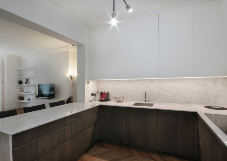 AQSO arquitectos office. The kitchen opens onto the living room thanks to a large opening with structural reinforcement in the load-bearing wall. The kitchen units combine dark wood, marble worktop and matt white lacquered doors.