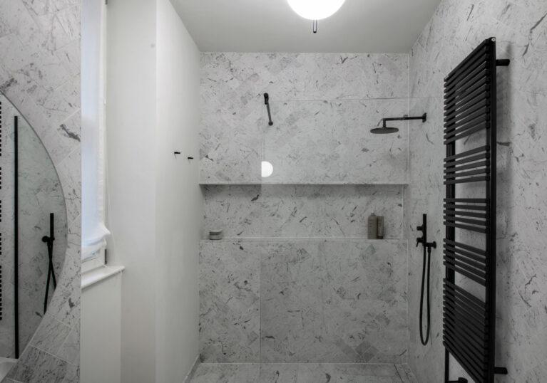 AQSO arquitectos office. El baño está revestido de mármol Statuario de origen italiano siguiendo un patrón de espina de pez. La grifería y los accesorios son de acero lacado en negro mate.