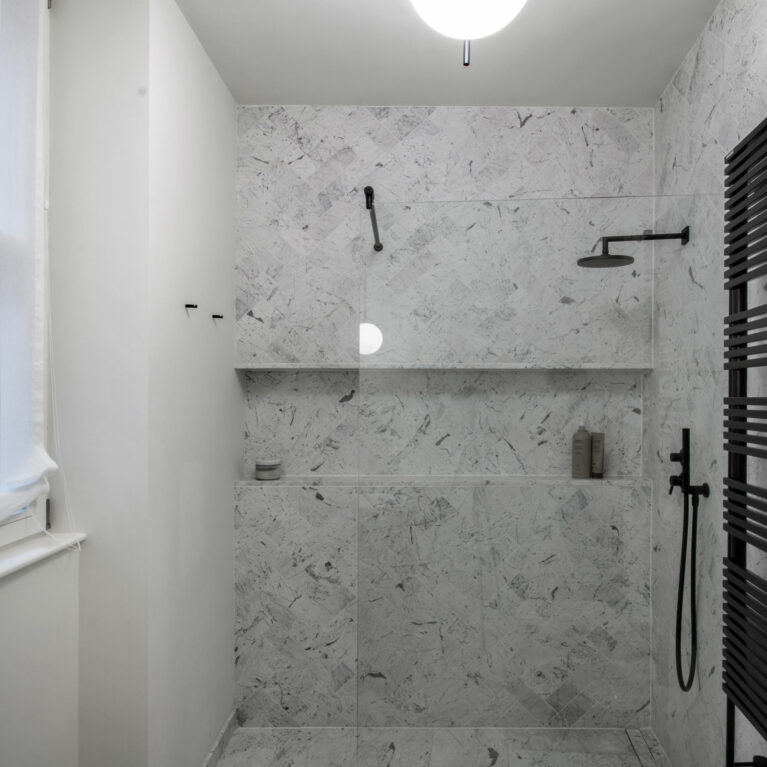 AQSO arquitectos office. The bathroom is clad in Italian Statuario marble in a herringbone pattern. The taps and fittings are in matt black lacquered steel.